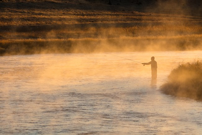 An angler fly fishes in a river at sunrise as fog rises from the water.