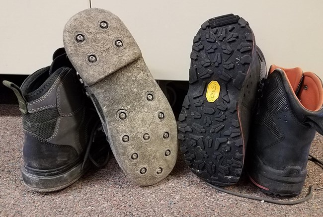 Two pairs of wading boots are seen side by side. One has felt soles and one has rubber soles.