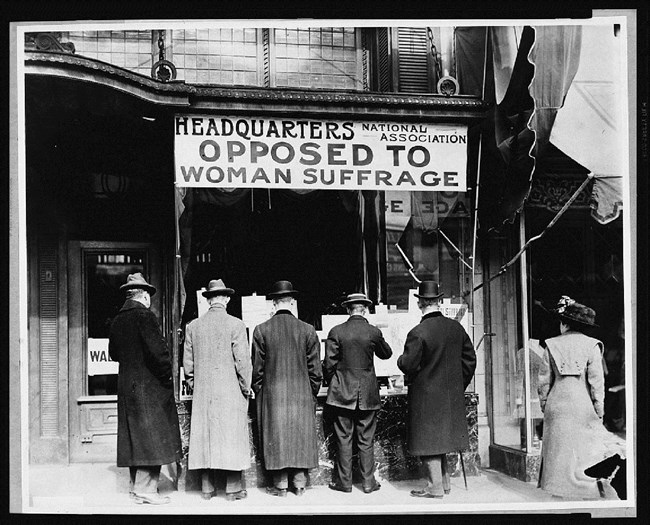 Men standing with their backs to camera under sign opposing women's suffrage. Library of Congress.