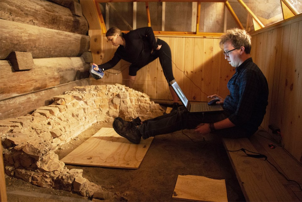 A man sits in a wooden boxy space with a laptop on his knees and feet near a crumbled brick hearth.