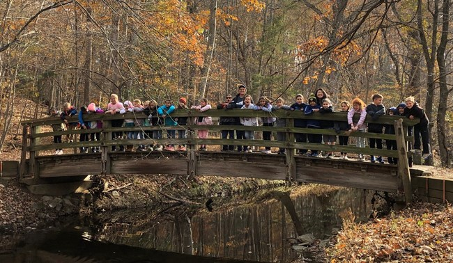 A group of students pose on a footbridge over Wolftrap Run while exploring the park's natural side during a field trip.