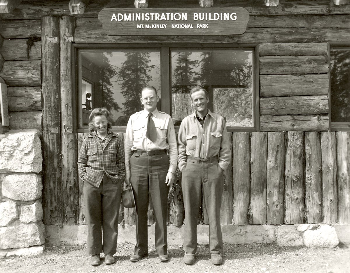 two men and a woman standing outside a log cabin with a sign that reads administration building