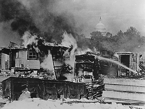 Destroyed buildings burn. The US Capitol dome looms in the background.