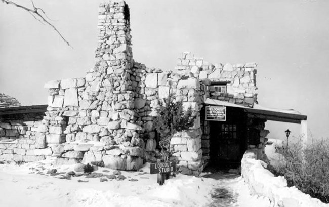 Stone building on the canyon's rim. On the left, there is a large chimney attached.