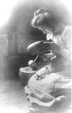 Mary Colter constructing a metal bowl, wearing a calico dress.