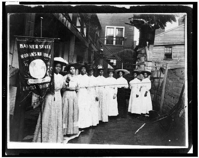 "Nine Afro-American women posed, standing, full length, with Nannie Burroughs holding banner reading, ""Banner State Woman's National Baptist Convention"""