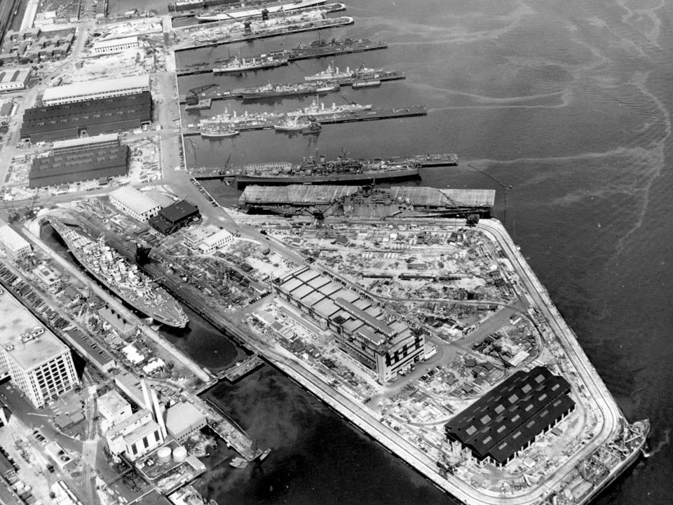 Photograph looking at piers dry docks and industrial buildings on the edge of a harbor. Warships are docked alongside the piers.