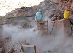 Lone archaeologist for artifacts at the dusty Axehandle Alcove site with wooden equipment.