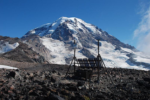 Monitoring equipments set up on two tripods on a rocky mountain slope beneath a glaciated summit.