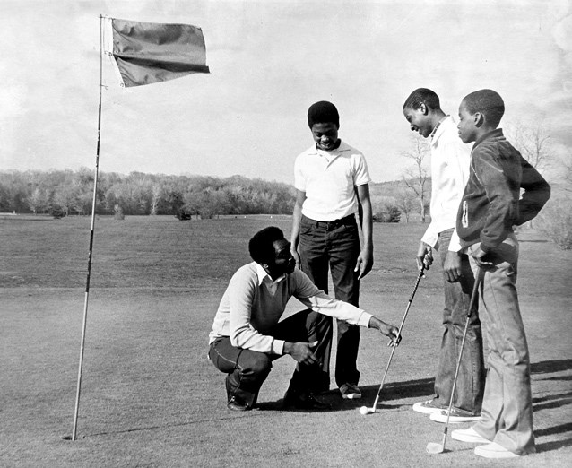 A man instructs boys to play golf