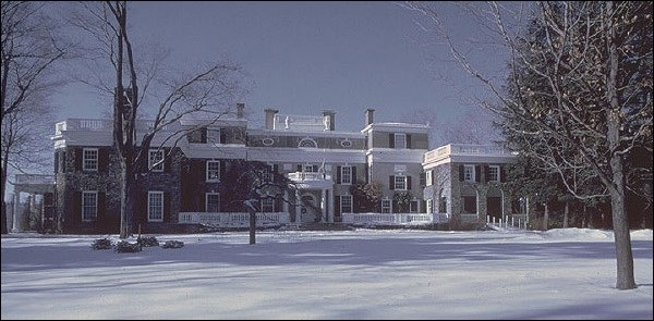 Large brick house covered  in snow.