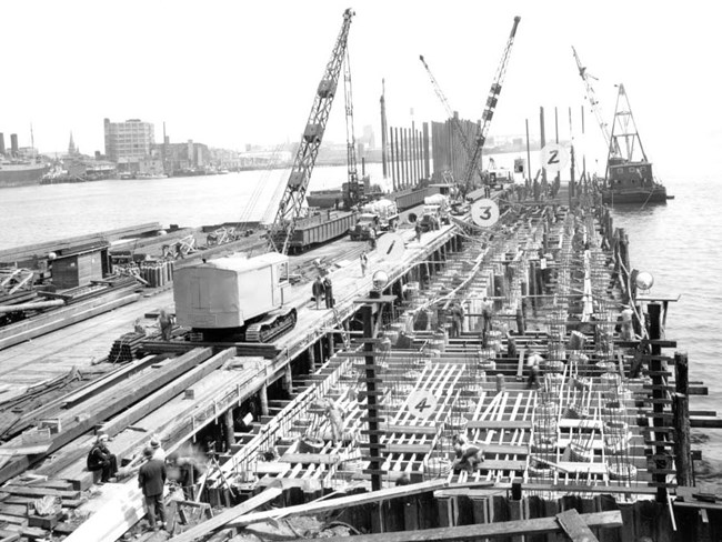 Photograph of workers and cranes on a pier in the midst of construction extending into Boston Harbor. Pile driving equipment is on a floating lighter at the edge of the pier.
