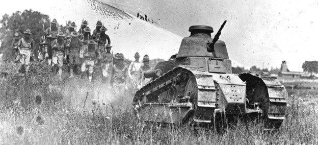 A Renault FT-17 tank rolls through the prairie, followed by infantry on foot.