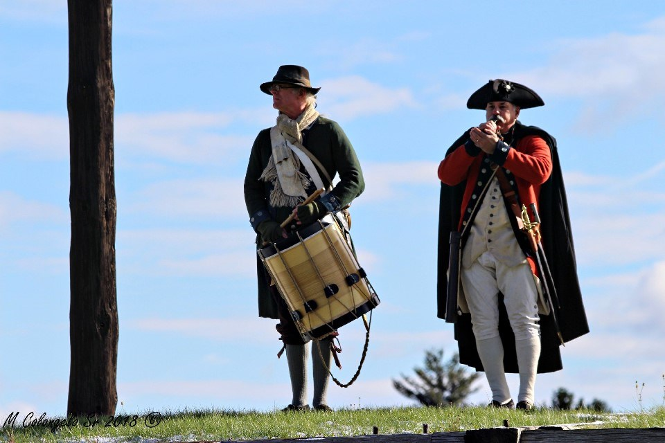 2 men stand on a grassy wall. One holds a drum. A second in a black cape, plays a bugle.
