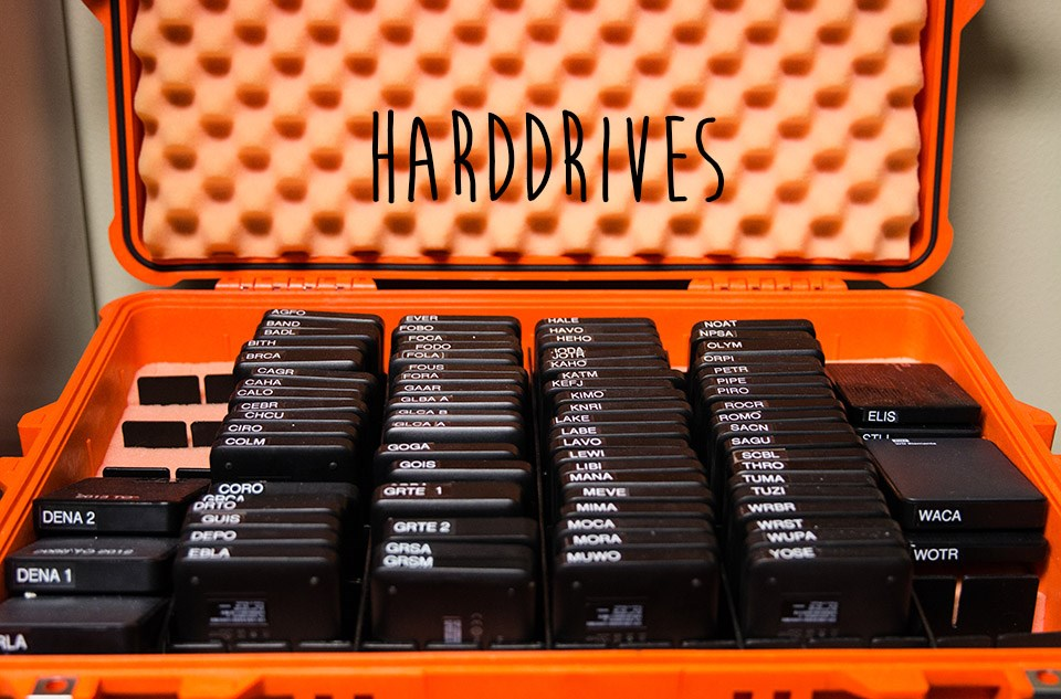 a bright orange case with several dozen black harddrives in it