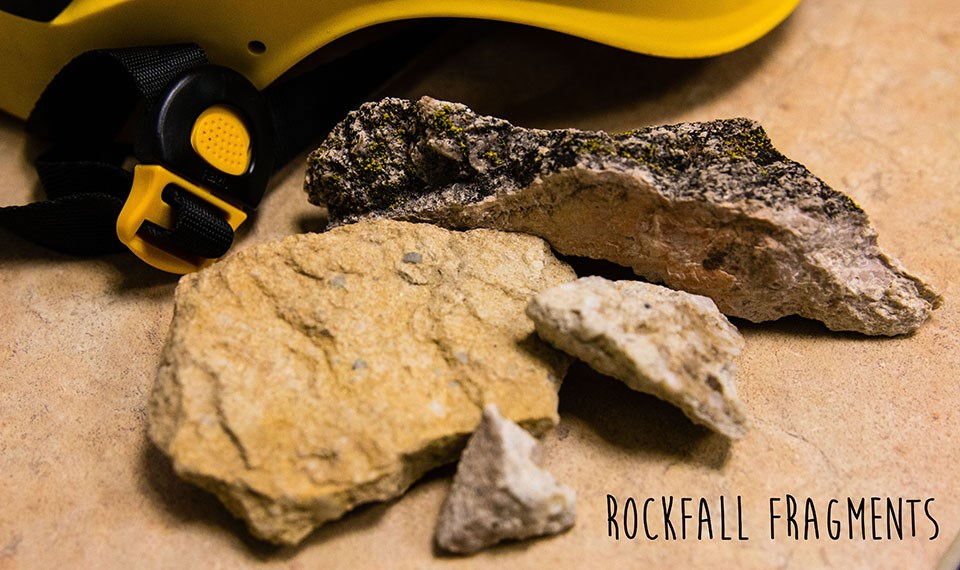 small rock fragments on desk with yellow helmet in background