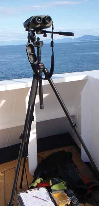 a pair of binoculars on a tripod set against the side of a boat with the ocean in the distance