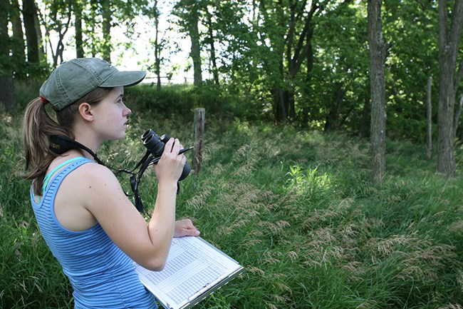 A woman with binoculars and clip board looks into the distance