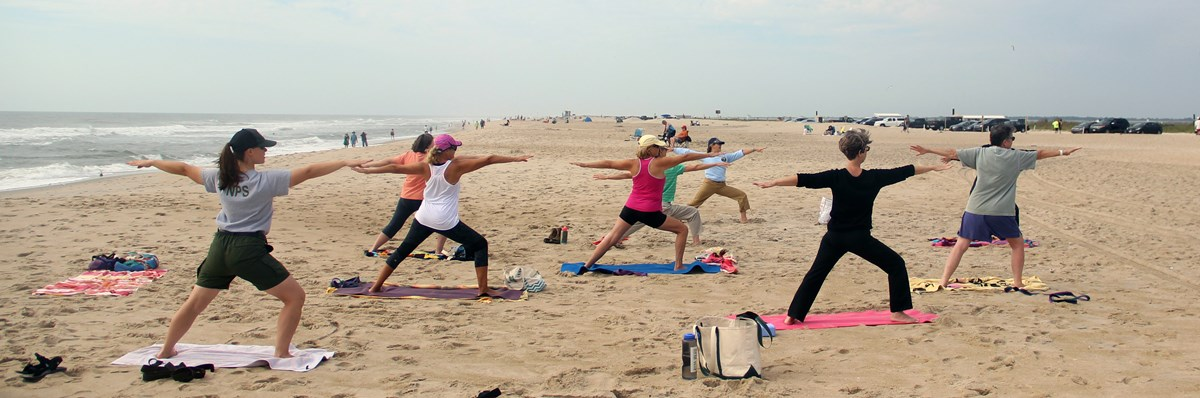 Group doing yoga on the beach with a ranger