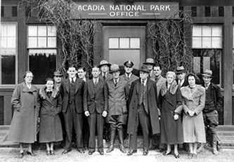 A group of people stand in front of a building at Acadia National Park