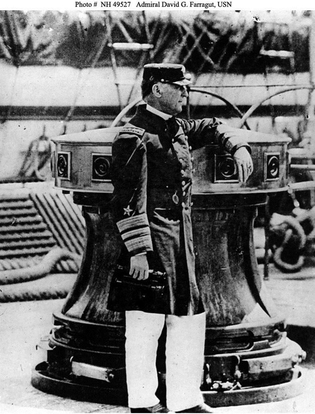 Black and white: A man is standing on a deck of a ship. His uniform shirt and hat are dark. His pants are white.