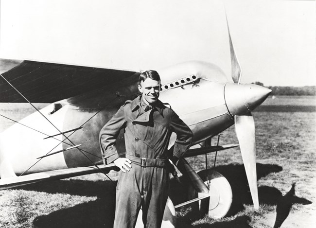Black and white photo of man in flight suit standing in front of an aircraft.