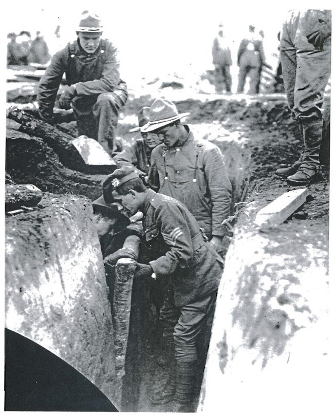 An instructor demonstrates proper trench reinforcement techniques for new recruits