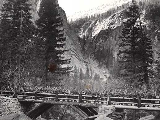 Black and white image of bridge below large waterfall.