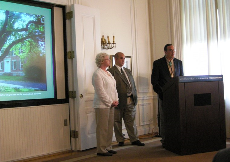 Three people standing in front of a screen with a podium in front.