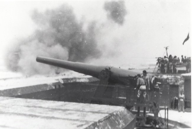 Black and white photo of a large steel cannon firing.
