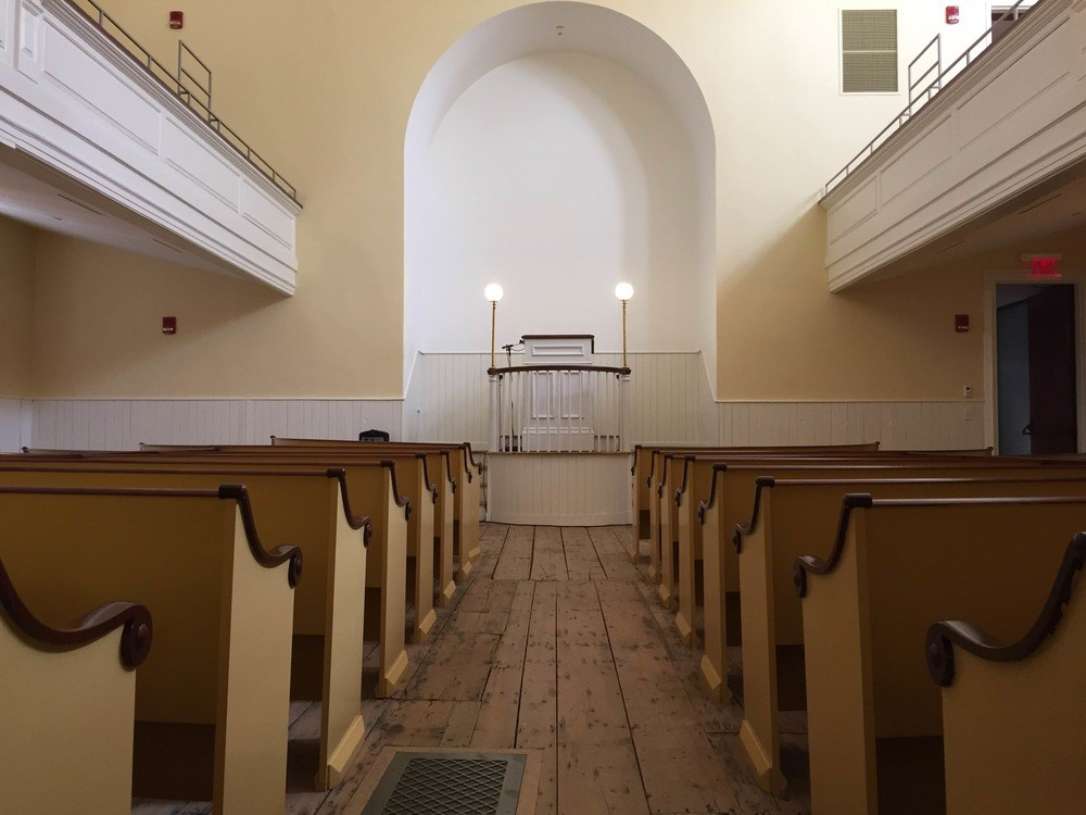 Interior of a church from behind rows of pews looking towards an altar.