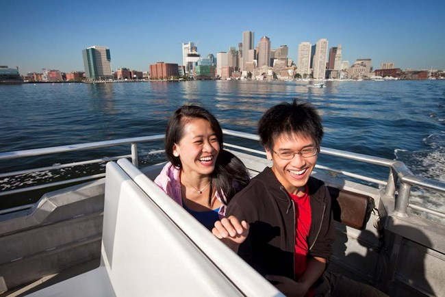 Two visitors sitting on a ferry out in open water with a cityscape in the background.