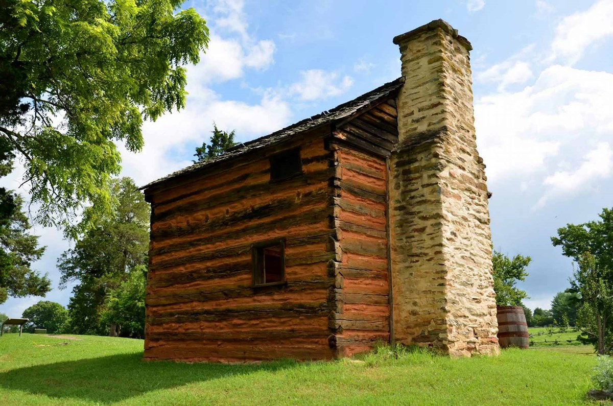 Log cabin with stone chimney surrounded by green grass and clear blue sky.