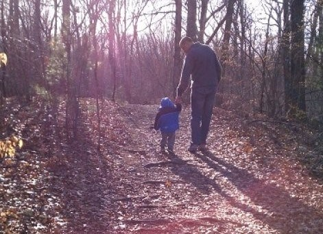 Man helps small child along a trail