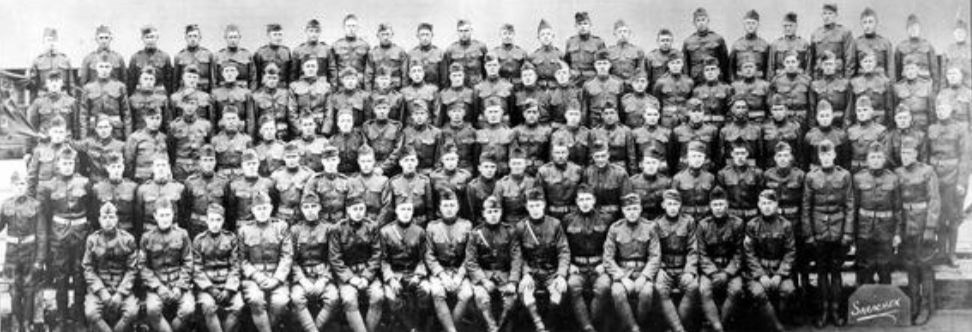 A large group of men in army uniform pose for a photo