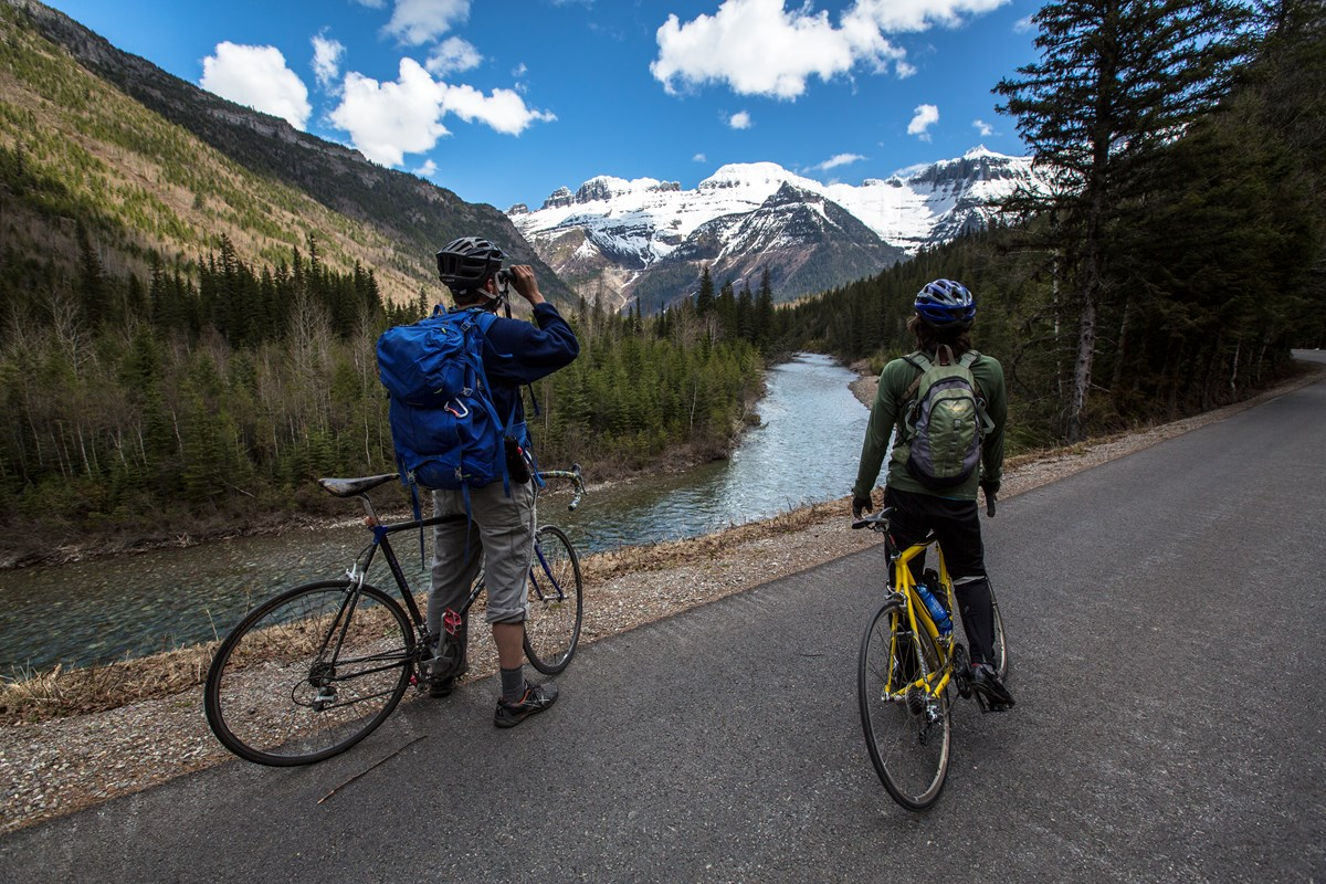 two bicyclists looking at ice top mountain from adistance with binoculars