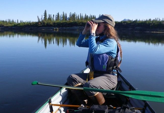 A woman looks through binoculars while sitting in a canoe on a lake