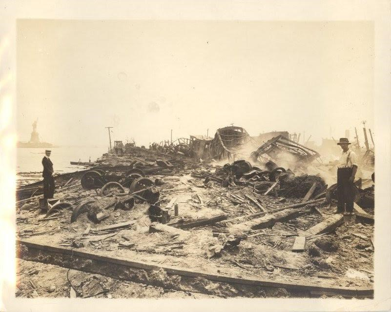 Pile of rubble with a man standing nearby and the Statue of Liberty in the distance