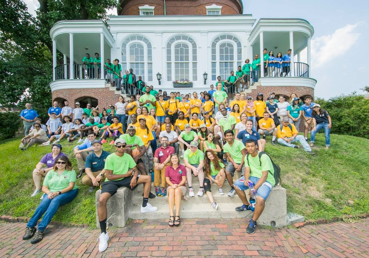 A large group of youth pose in front of historic home.