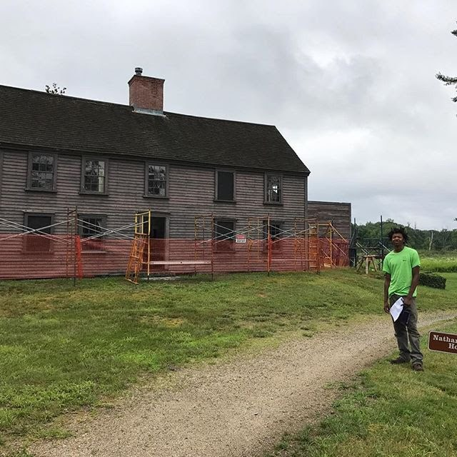A young man poses in front of an historic structure being repaired.
