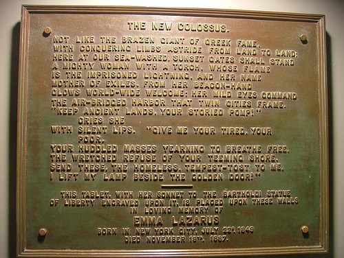 "A bronze plaque with the words of the poem ""The New Colossus"" raised on it."