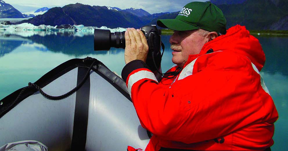 A glaciologist takes photos of a glacier while wearing a large, bright red winter coat.