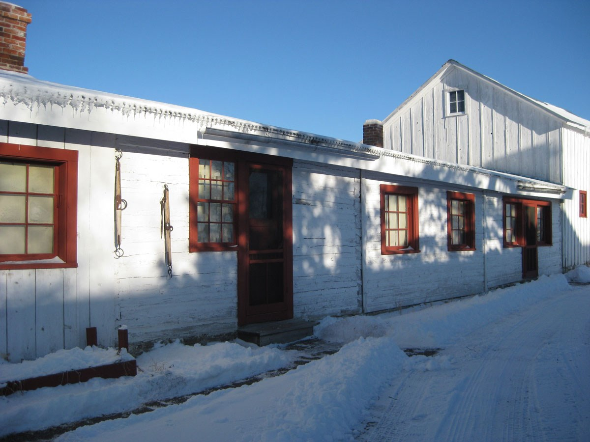 Bunkhouse with afternoon shadows on clear, snow covered winter day.