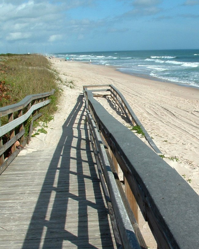 ramp to sandy beach and ocean waves