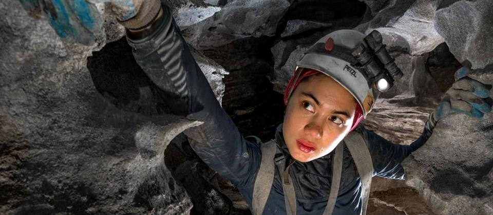 intern wearing helmet and gloves in a cave