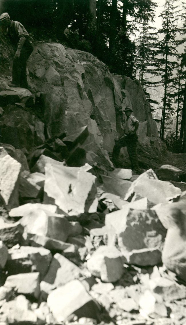 A man working at road construction along the Carbon River with rocks in the foreground.