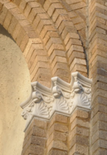 Three brown brick and white stone architectural pillars.