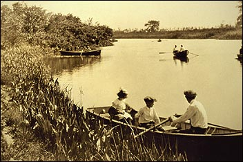 B&W photo of people rowing in boats on a lake.