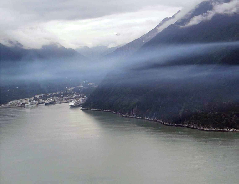 A view about the skagway harbor with a layer of haze about a cruise ship