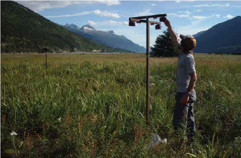 a person reaches up to adjust a gas measuring device in a grassy field, surrounded by mountains